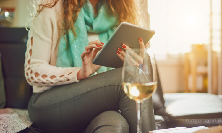 Woman Working on Tablet with white wine